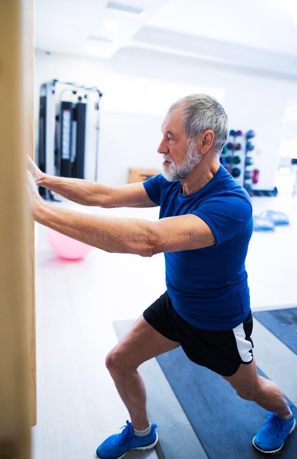 Älterer Mann in der Turnhalle ausarbeitend, seine Beine ausdehnend lizenzfreie stockfotos