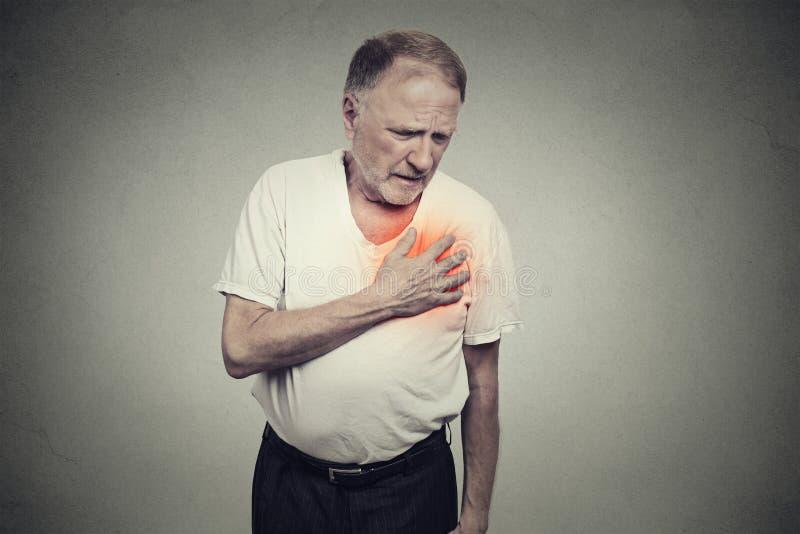 Älterer Mann, der unter den schlechten Schmerz in seinem Kastenherzinfarkt leidet lizenzfreie stockbilder