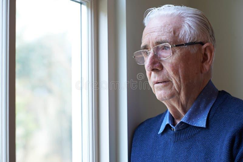 Älterer Mann, der unter der Krise schaut aus Wi heraus leidet stockfotografie