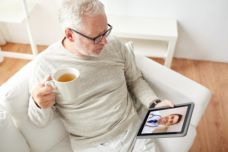 Älterer Mann, der Videoanruf mit Doktor auf Tablette hat stockfotografie