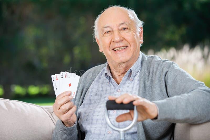 Älterer Mann, der vier Asse beim an sitzen hält lizenzfreie stockfotos