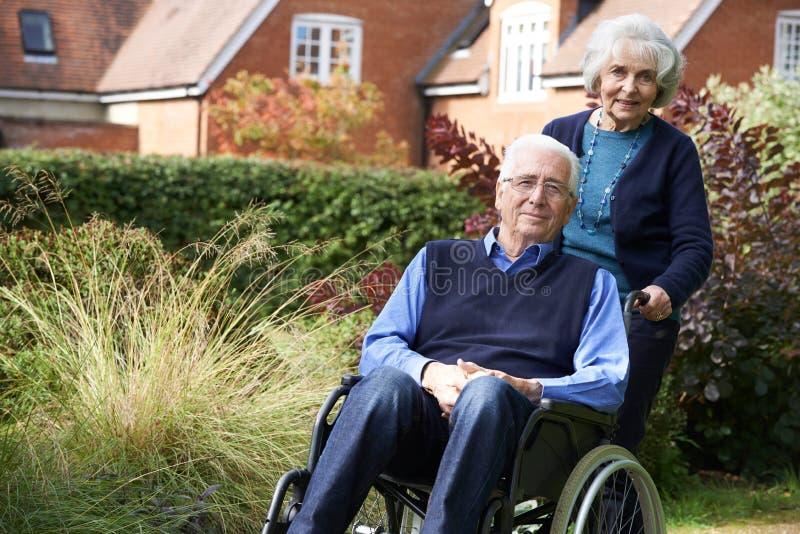 Älterer Mann, der von der Frau im Rollstuhl gedrückt wird stockfoto