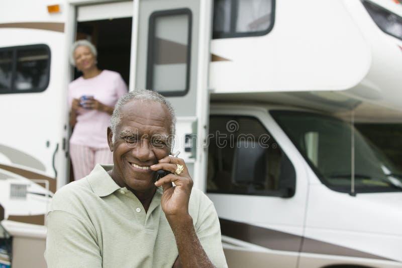 Älterer Mann, der vor einem Wohnwagen sitzt lizenzfreie stockfotos