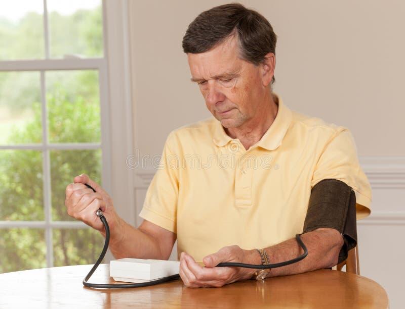 Älterer Mann, der zu Hause Blutdruck nimmt lizenzfreie stockbilder