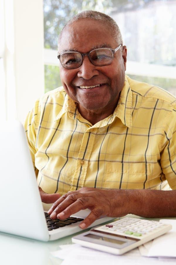 Älterer Mann, der zu Hause Laptop verwendet lizenzfreie stockfotos