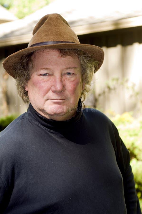 Älterer Mann des Mittelalters mit modernem Hut im Yard stockfoto