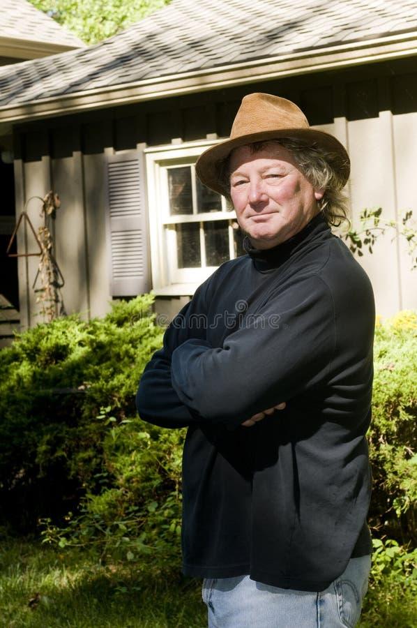 Älterer Mann des Mittelalters mit modernem Hut im Yard stockbild