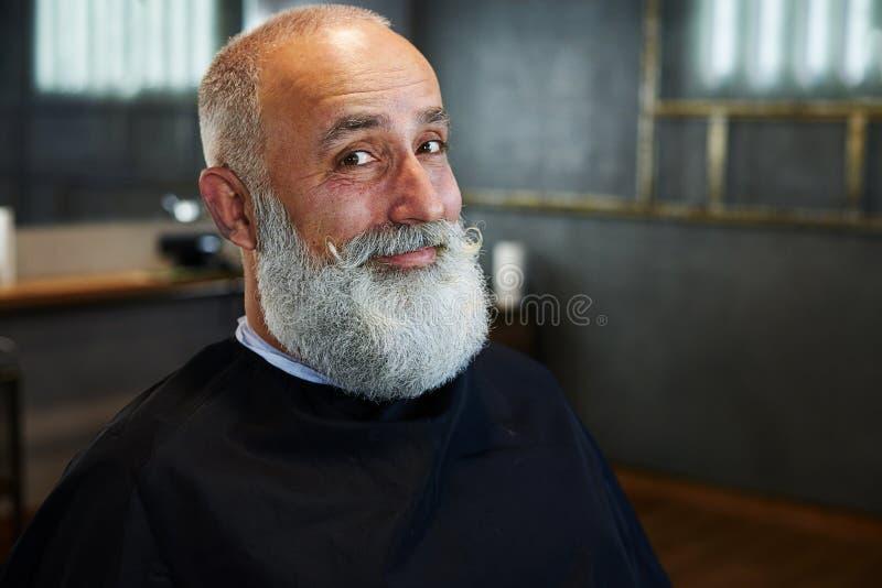 Älterer Mann des smiley mit grau-haarigen Bart und dem Schnurrbart stockfoto