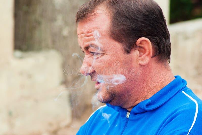 Älterer Mann gekleidet in der Abendtoilette, die cigaretes raucht lizenzfreie stockfotografie