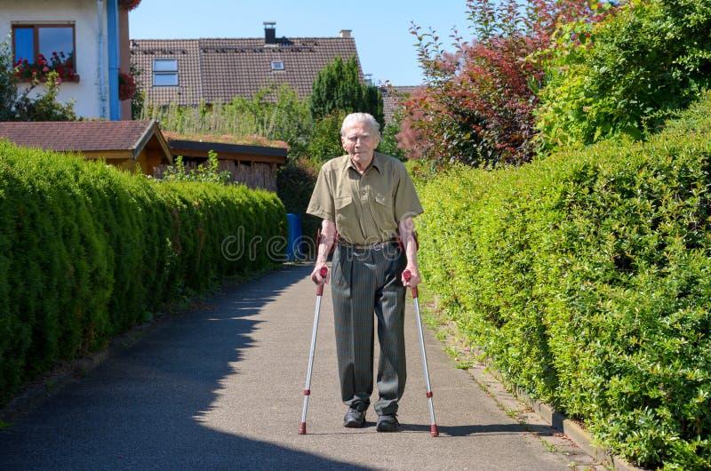 Älterer Mann im Ruhestand, der auf Krücken geht lizenzfreies stockbild