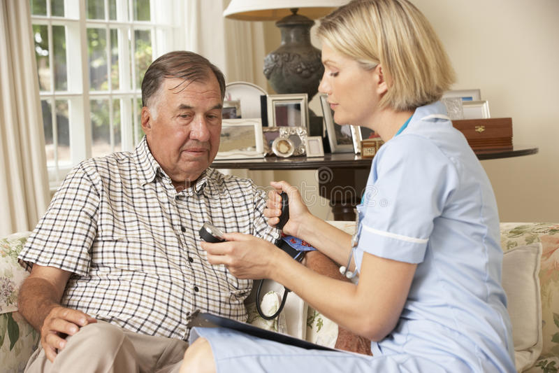 Älterer Mann im Ruhestand, der Gesundheits-Check mit Krankenschwester At Home hat lizenzfreie stockfotos