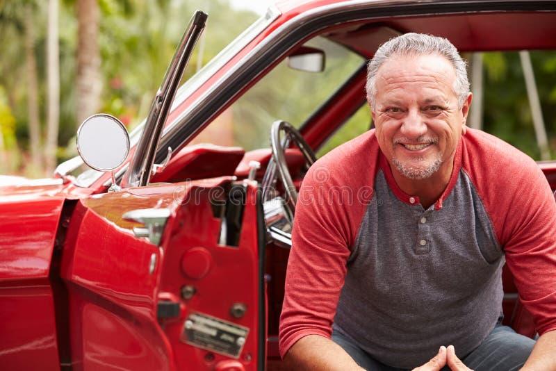 Älterer Mann im Ruhestand, der in wieder hergestelltem Oldtimer sitzt lizenzfreie stockfotos