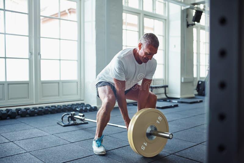 Älterer Mann im Sportkleidungsgewichtheben allein in einer Turnhalle lizenzfreie stockfotos