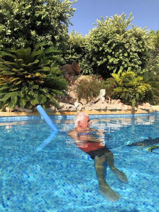 Älterer Mann im Swimmingpool, halten kühl stockfoto