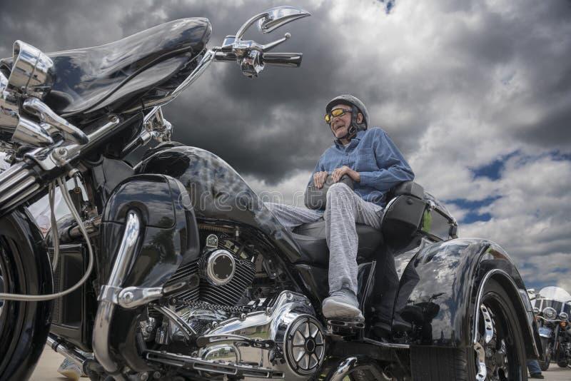 Älterer Mann lächelt breit, während er auf der Rückseite eines starken sitzt lizenzfreie stockbilder