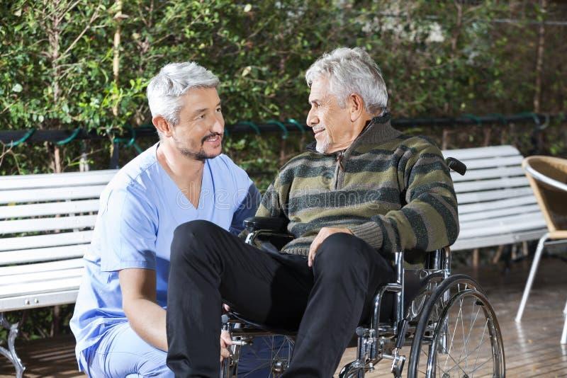 Älterer Mann männlicher Physiotherapeuten-Looking At Disableds in Wheelchai stockbilder