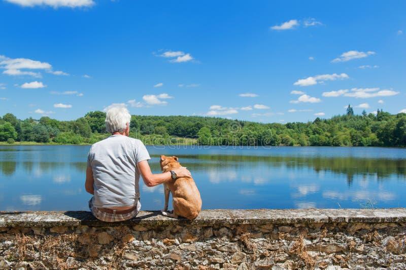 Älterer Mann mit altem Hund in der Naturlandschaft stockfotos