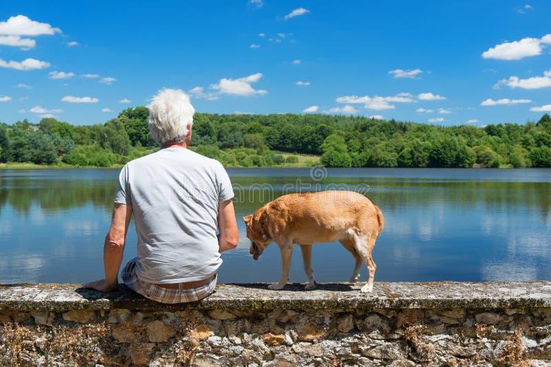 Älterer Mann mit altem Hund in der Naturlandschaft lizenzfreie stockfotos