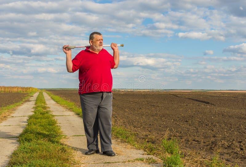Älterer Mann mit dem Spazierstock, der auf einer Landstraße steht stockfotografie