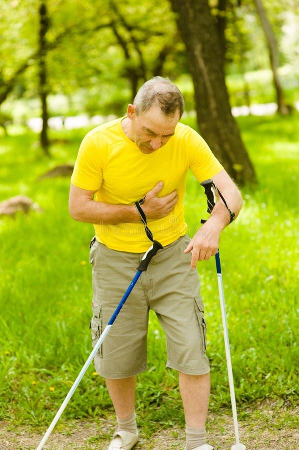 Älterer Mann mit den Schmerz auf Herzen während des nordischen Gehens stockbild