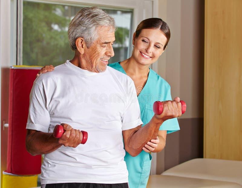 Älterer Mann mit Dumbbells in der Rehabilitation lizenzfreie stockfotografie