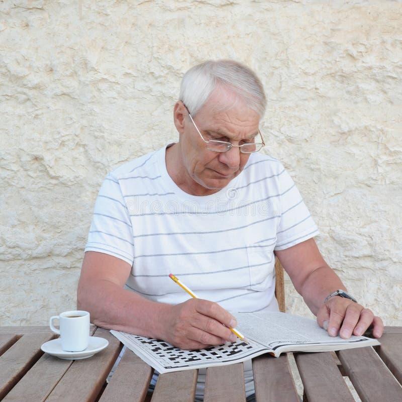 Älterer Mann mit einem Kreuzworträtsel lizenzfreie stockfotografie