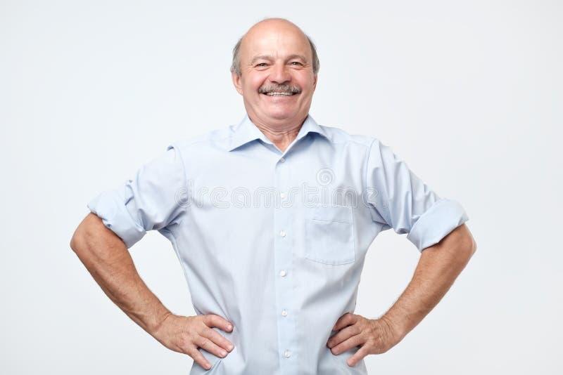 Älterer Mann mit einem stolzen, erfüllten und glücklichen Blick, mit beiden Händen auf Hüften stockbilder