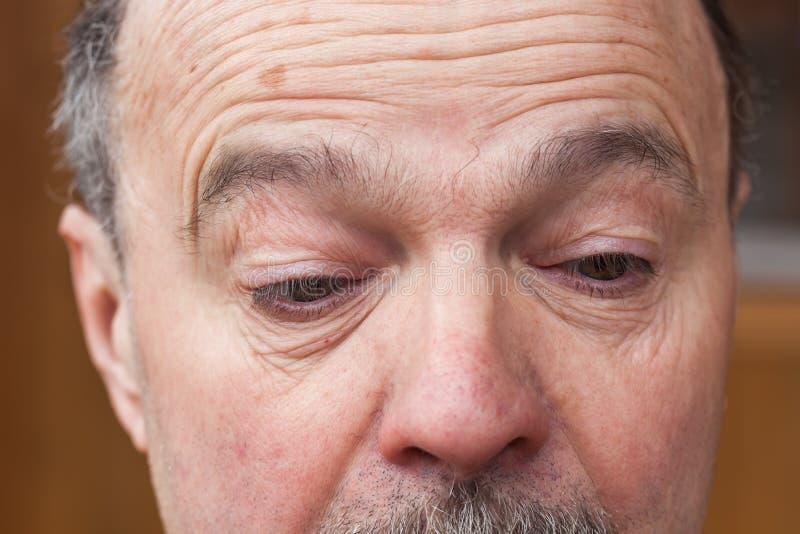 Älterer Mann mit einem Zweifel, der weg schaut stockbilder