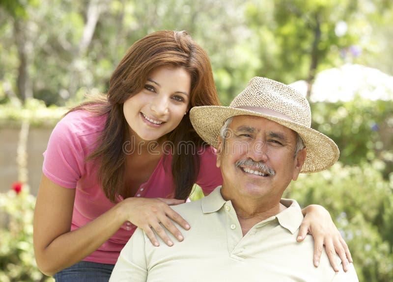 Älterer Mann mit erwachsener Tochter im Garten lizenzfreie stockfotografie