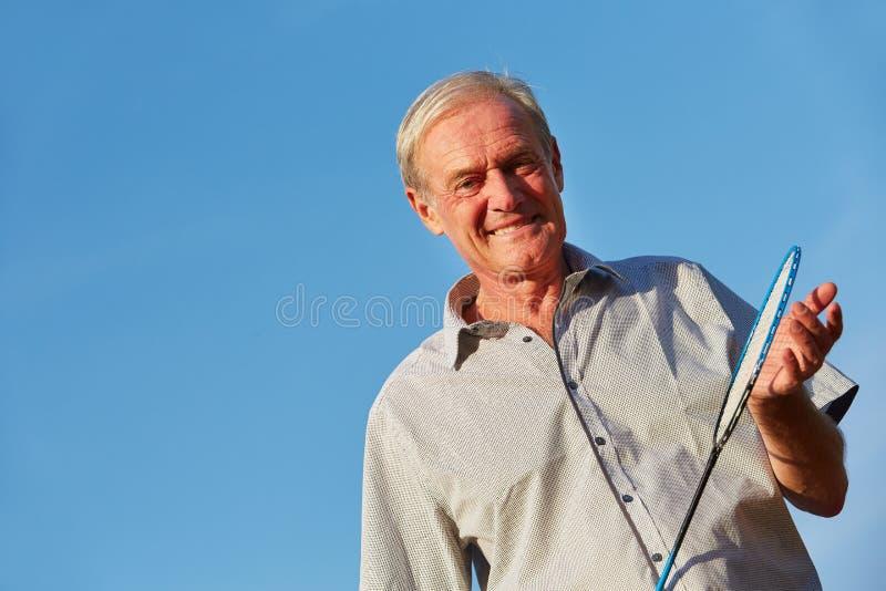 Älterer Mann mit Federballschläger stockfotografie