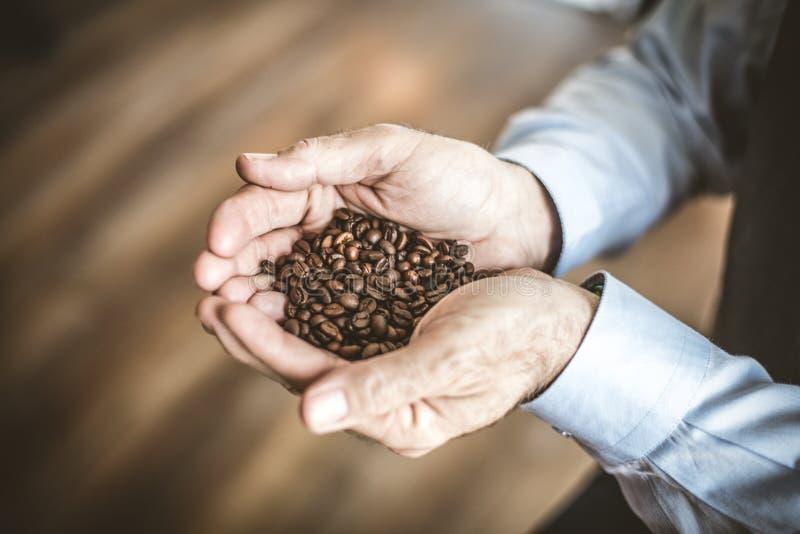 Älterer Mann mit ganzem Getreidekaffee in seiner Hand lizenzfreie stockfotos