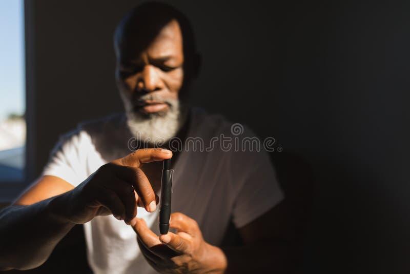 Älterer Mann mit glucometer Blutzuckerspiegel zu Hause überprüfend stockbild
