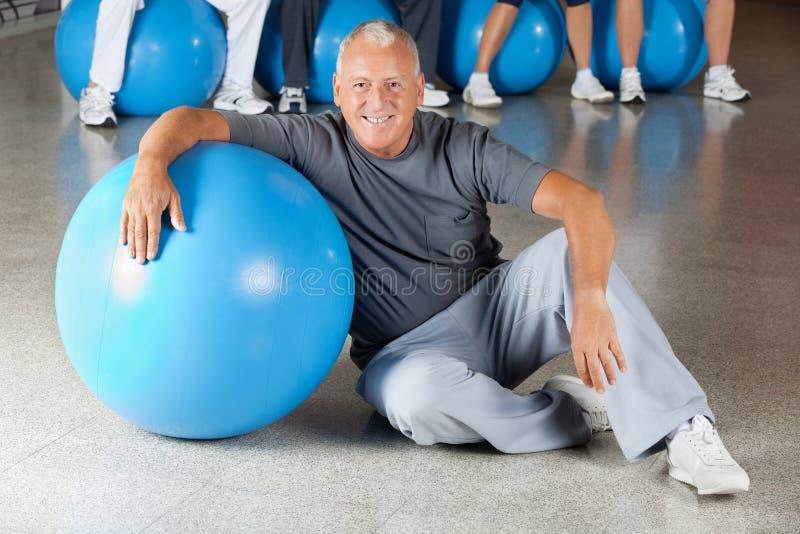 Älterer Mann mit Gymnastikkugel in der Eignung stockfoto