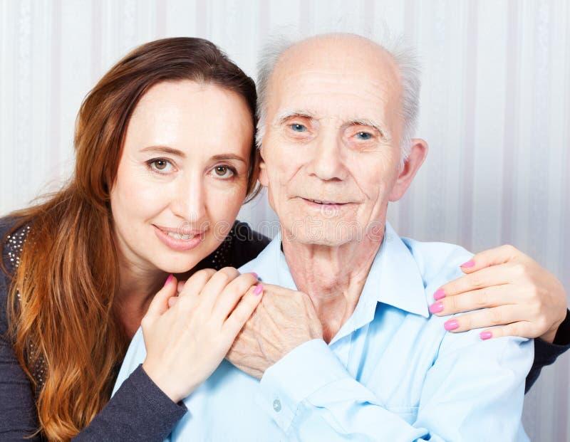 Älterer Mann mit ihrer Pflegekraft zu Hause lizenzfreies stockbild