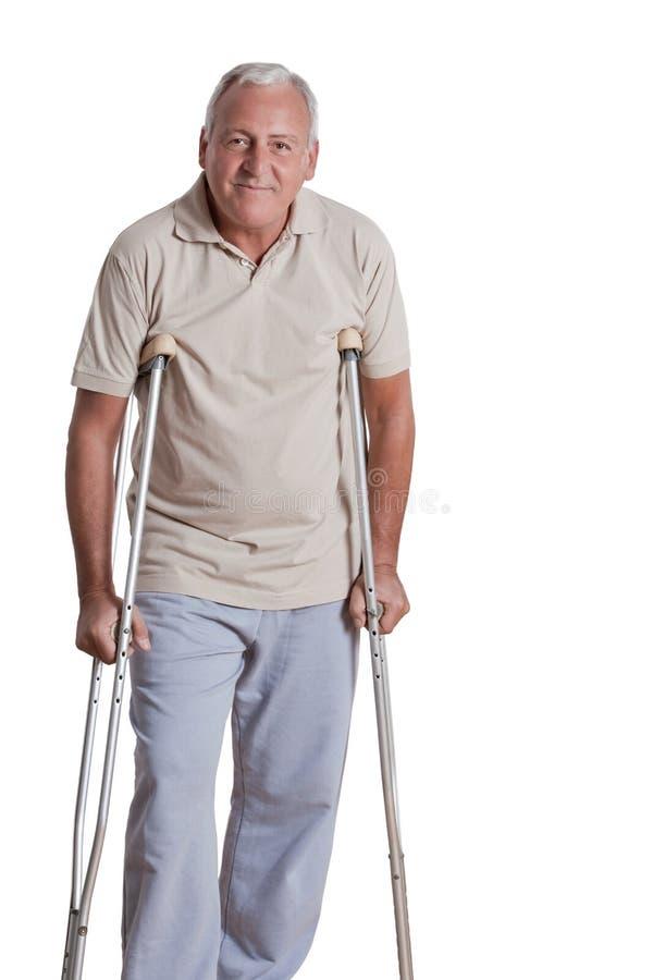 Älterer Mann mit Krücken lizenzfreie stockfotos