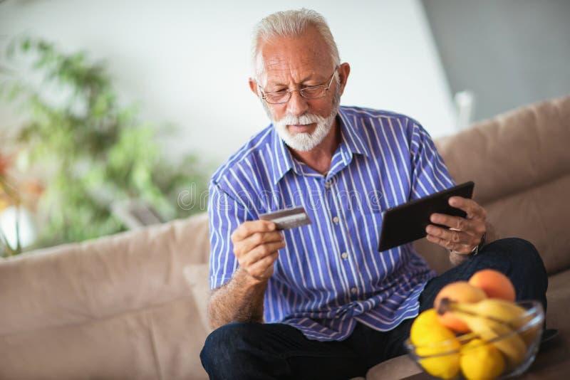 Älterer Mann mit Kreditkarte für Online-Banking lizenzfreie stockfotografie