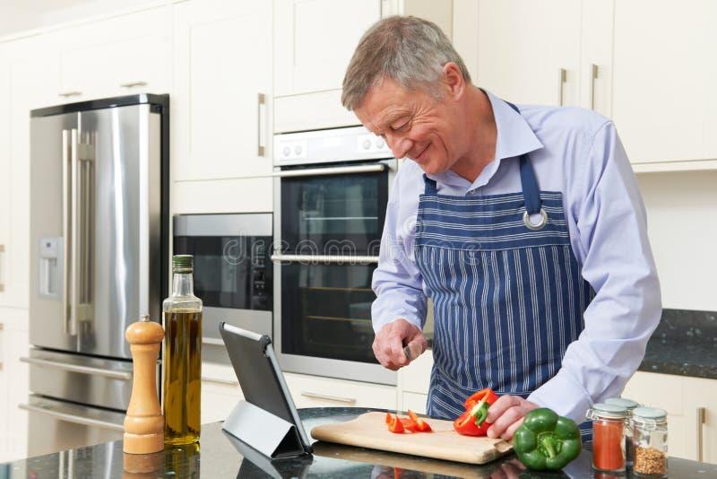 Älterer Mann nach Rezept auf Digital-Tablet lizenzfreies stockfoto