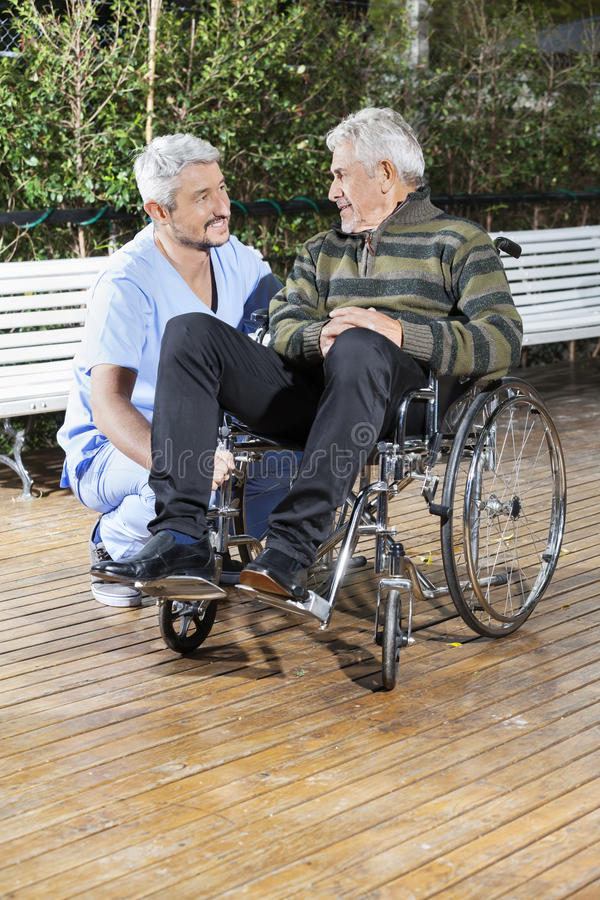 Älterer Mann Physiotherapeuten-Looking At Disableds im Rollstuhl lizenzfreie stockfotografie