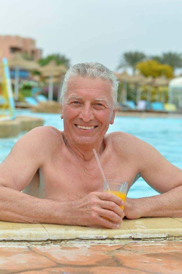 Älterer Mann am Rand des Swimmingpools stockfotos