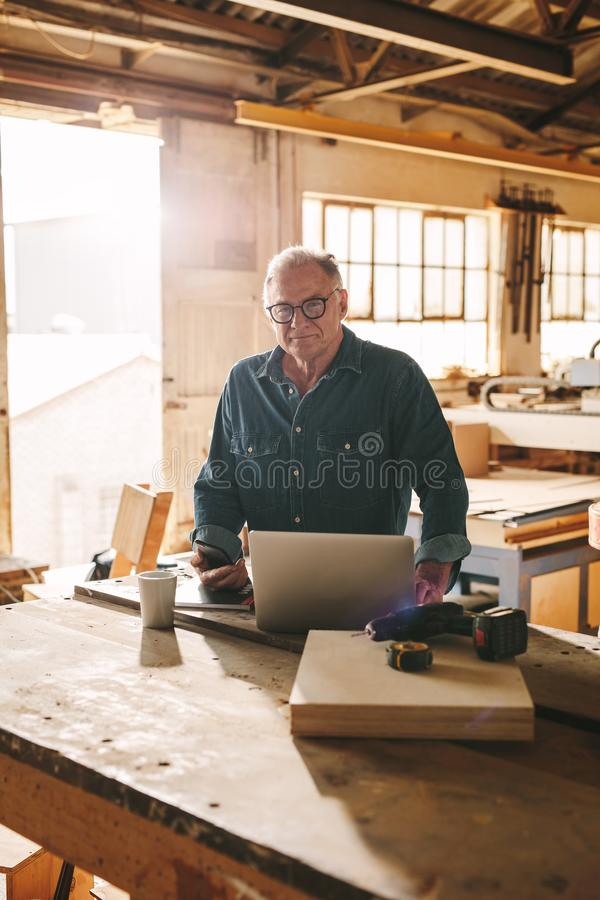 Älterer Mann an seiner Zimmereiwerkstatt stockfotografie
