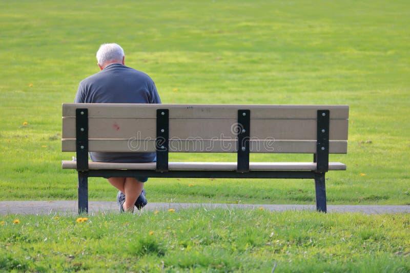 Älterer Mann sitzt allein im Park stockfotos