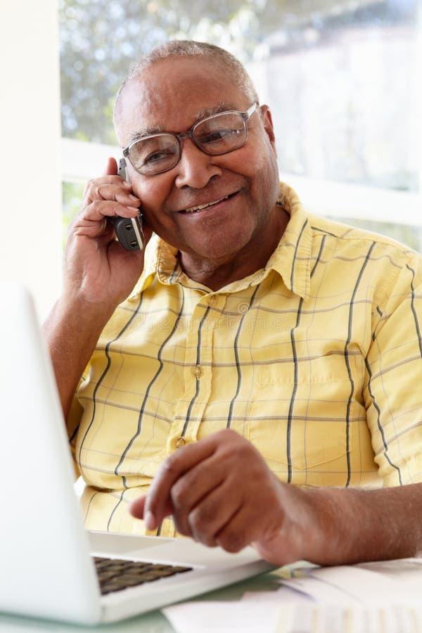 Älterer Mann am Telefon unter Verwendung des Laptops zu Hause lizenzfreie stockbilder