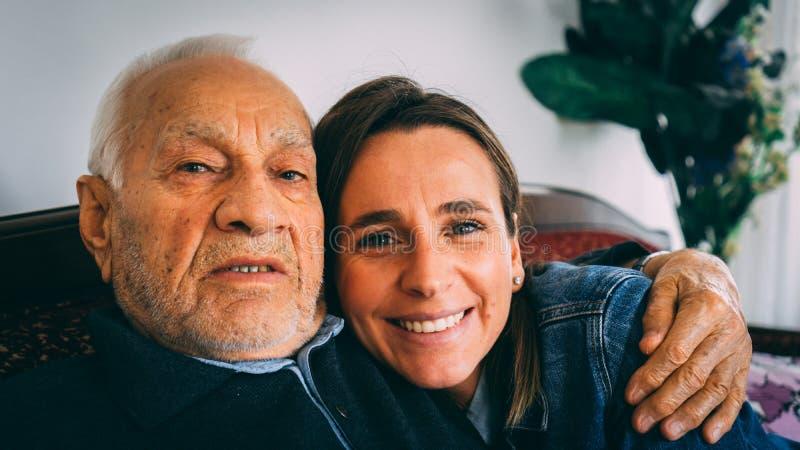 Älterer Mann umarmt seine erwachsene Enkelin zu Hause stockfoto