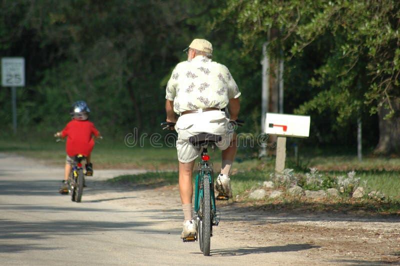 Älterer Mann-und Enkel-Fahrrad-Reiten lizenzfreies stockbild