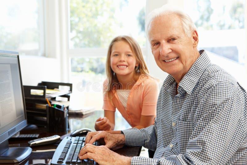 Älterer Mann und Enkelin, die Computer verwendet lizenzfreies stockfoto
