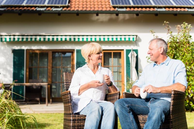 Älterer Mann und Frau, die vor Haus sitzt lizenzfreie stockfotos