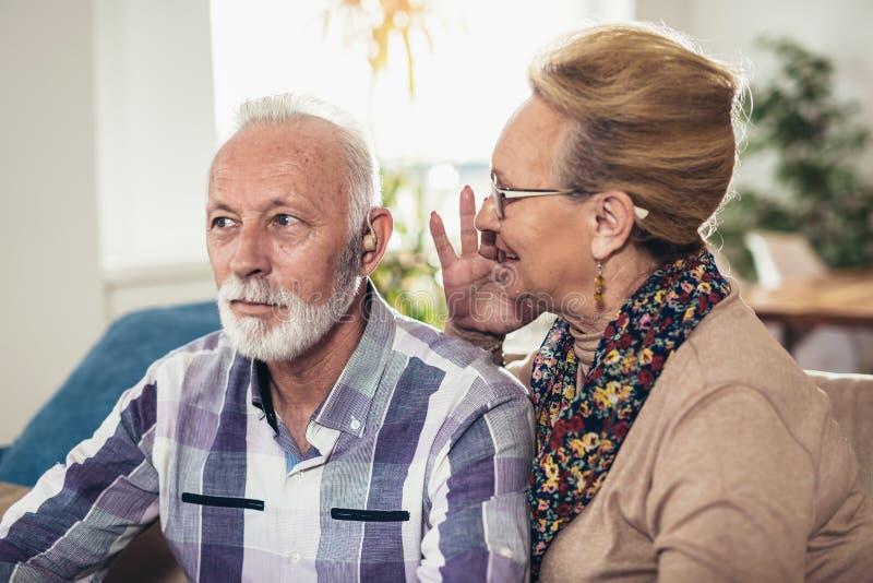 Älterer Mann und Frau oder Pensionäre mit einem Anhörungsproblem stockfoto