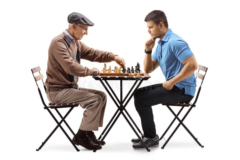 Älterer Mann und junger ein Kerl, der ein Spiel des Schachs spielt stockfotografie