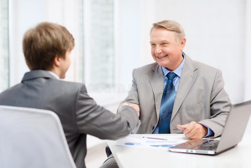 Älterer Mann und junger Mann, der Hände im Büro rüttelt stockbilder