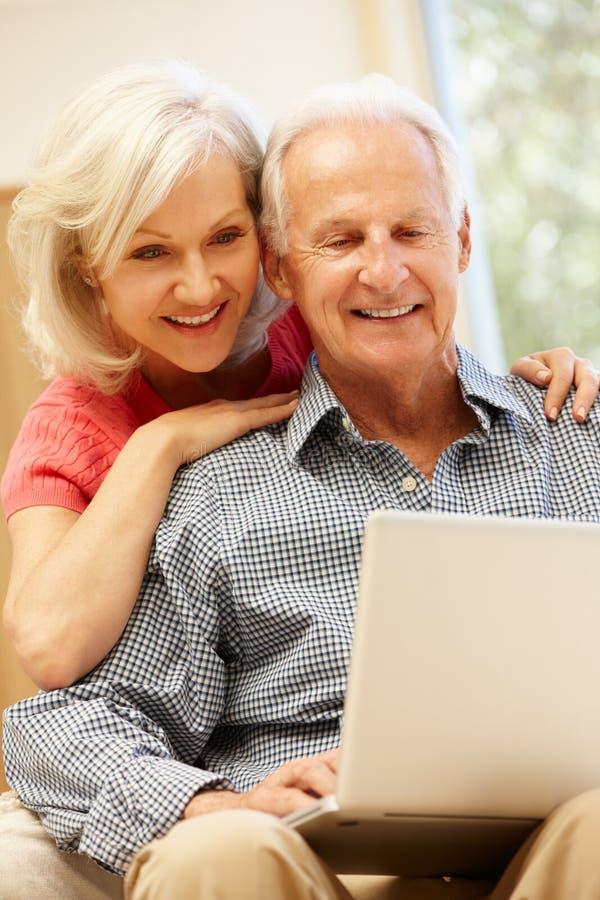 Älterer Mann und Tochter, die Laptop verwendet stockbild